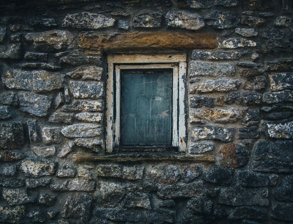 Stone wall with boarded up window