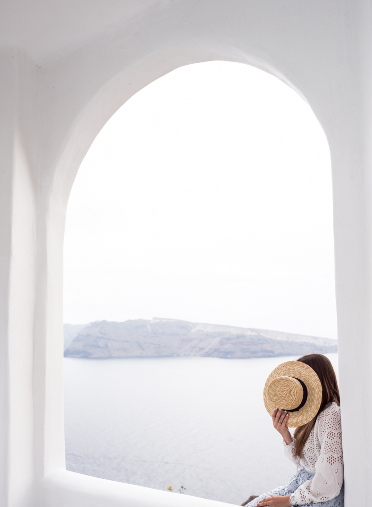 Girl holding hat sitting in alcove in Greece