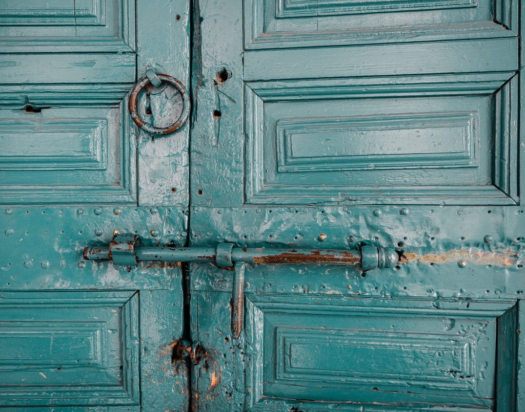 Turquoise colored wood door with bolt