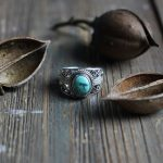 Turquoise silver ring and nuts on wood table