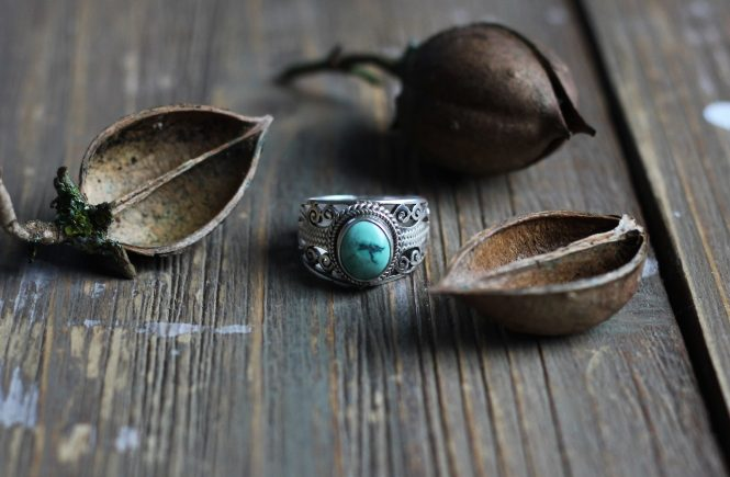 Turquoise stone, silver ring with nuts on top of wood table