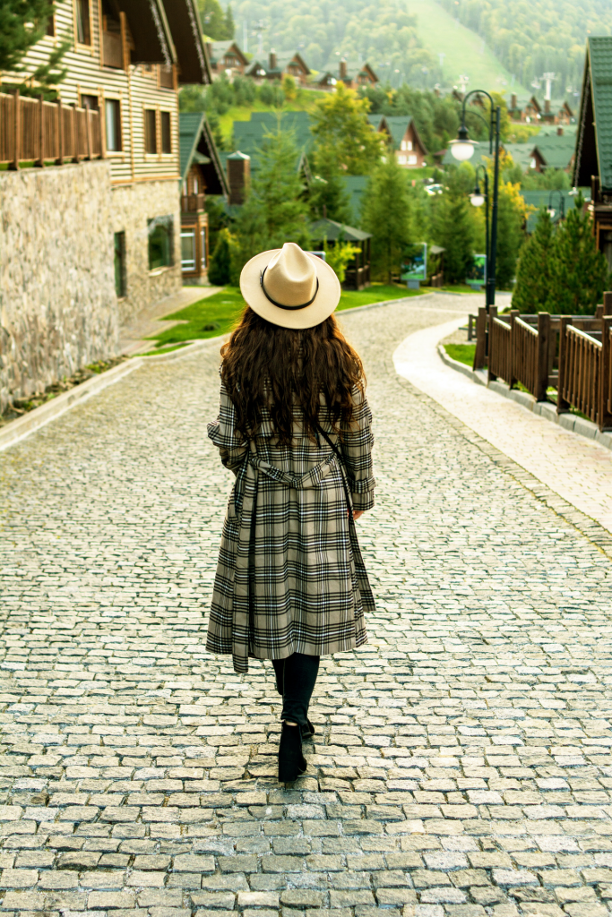 Girl with plaid coat and hat walking down cobblestone street