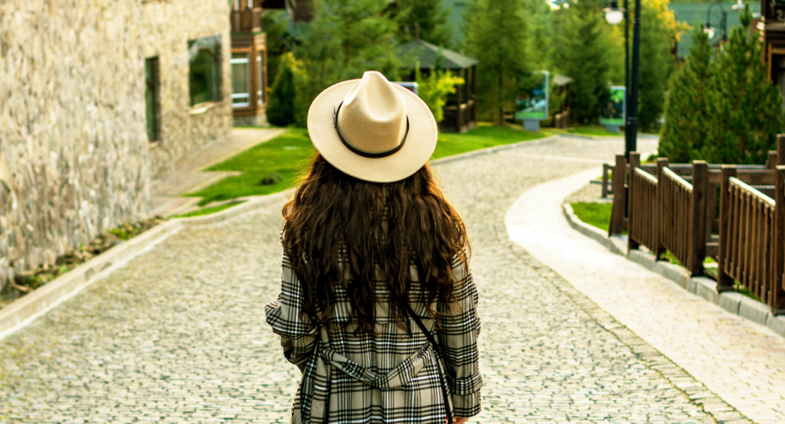 Girl wearing hat and plaid coat walking down cobblestone street