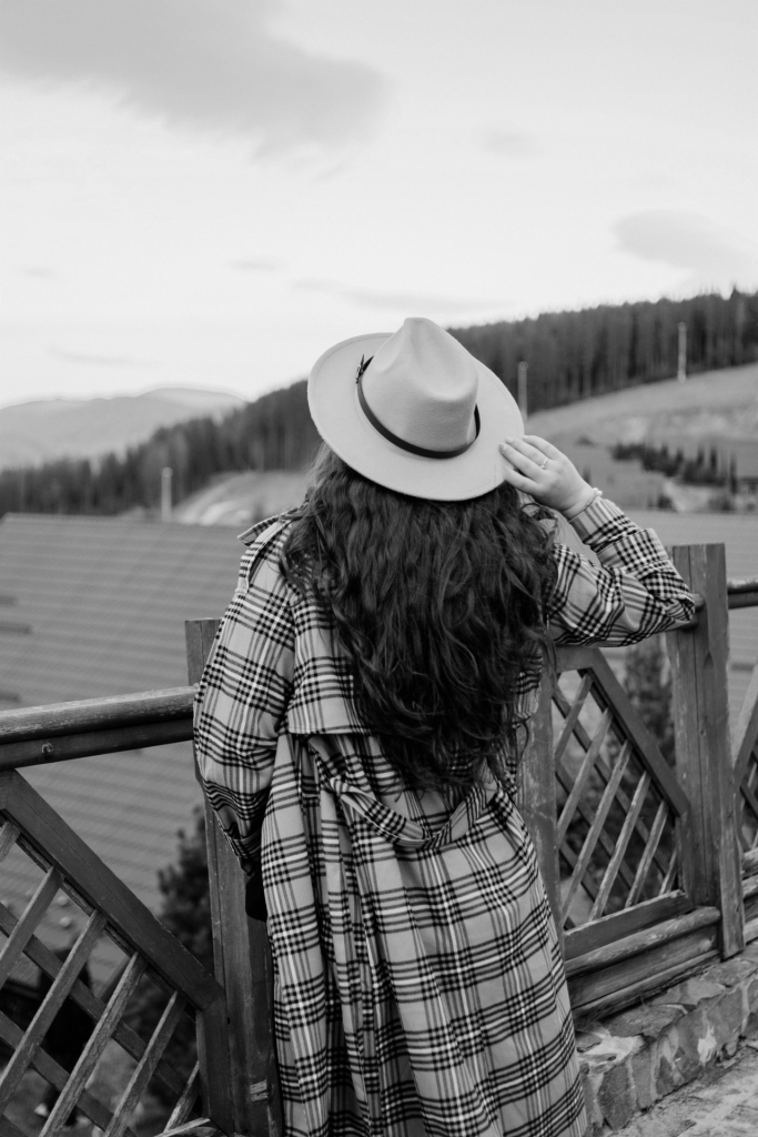 Girl wearing hat and plaid coat looking out at scenery