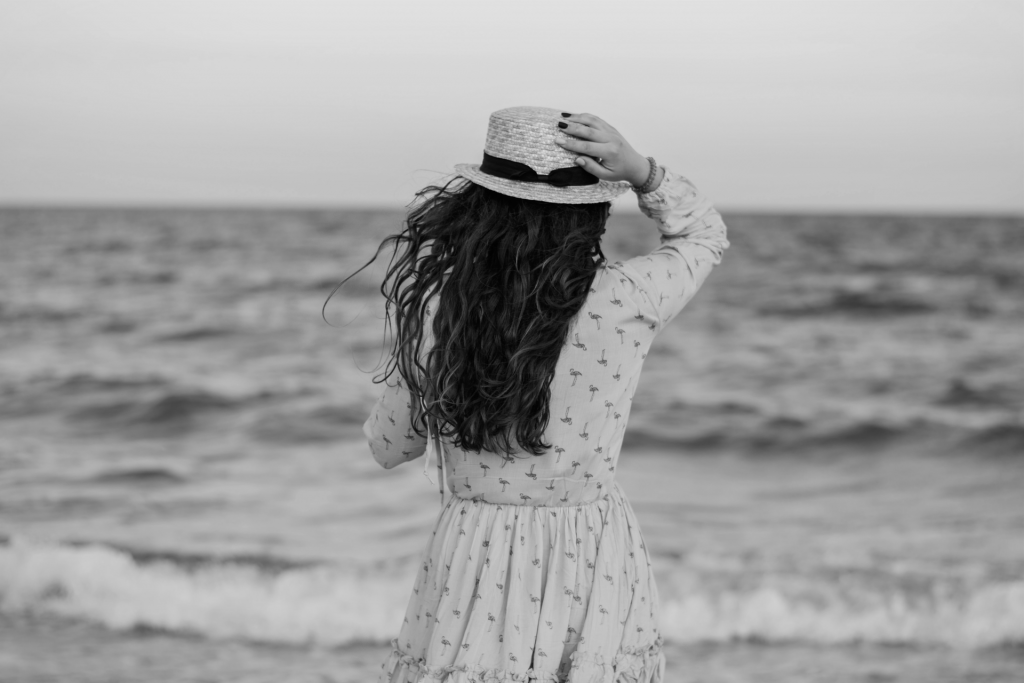 Black and white image of girl with hat looking out at sea