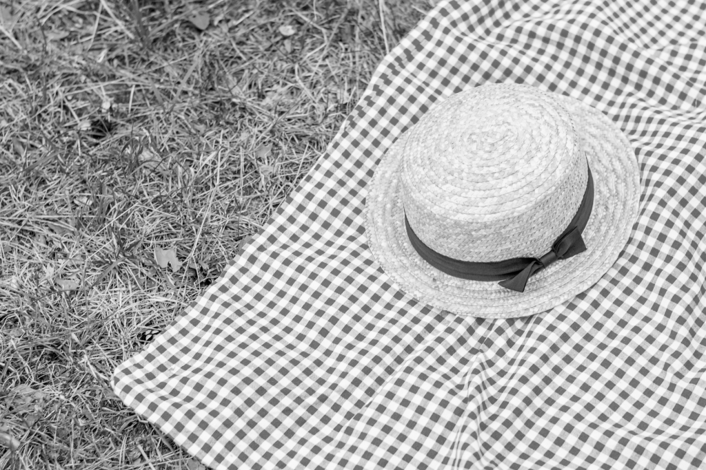 Black and white image of straw hat on checkered tablecloth