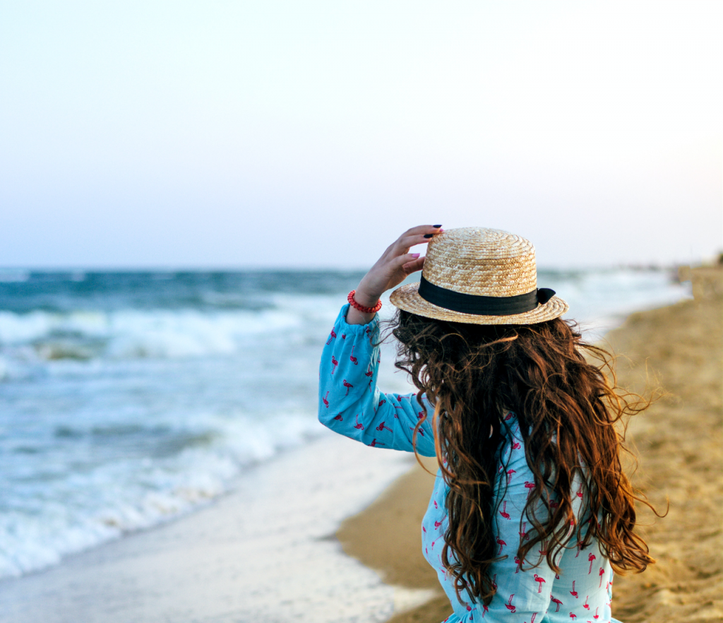 Girl with hat looking at ocean