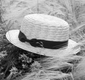 Black and white image of straw hat in wheat field