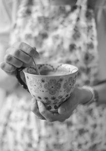Black and white image of lady holding teacup stirring with spoon