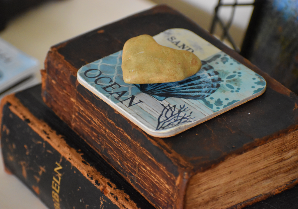 Heart rock on ocean coaster on two brown books