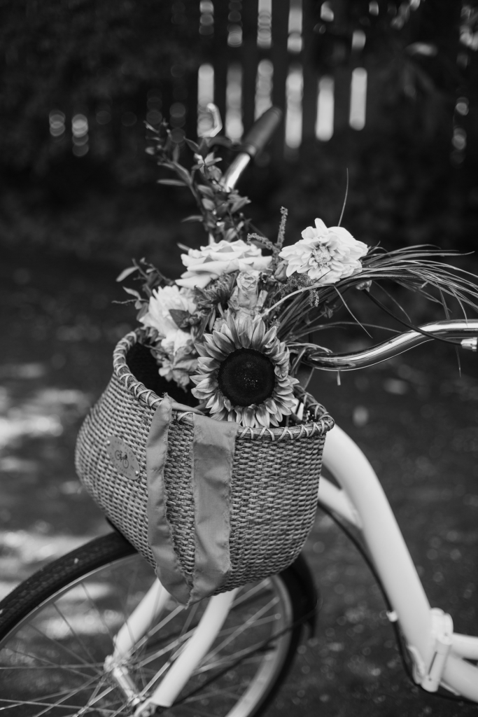 Black and white image of white bicycle with basket with flowers