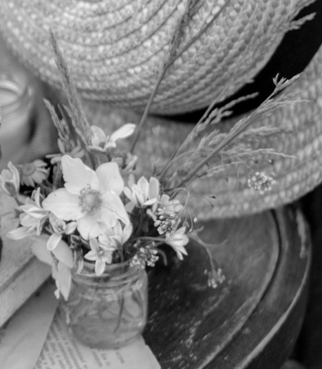 Straw hat and small bouquet flowers on wood chair