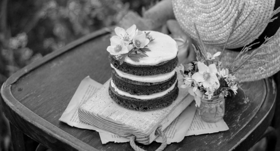 Cake, straw hat, small bouquet of flowers on chair