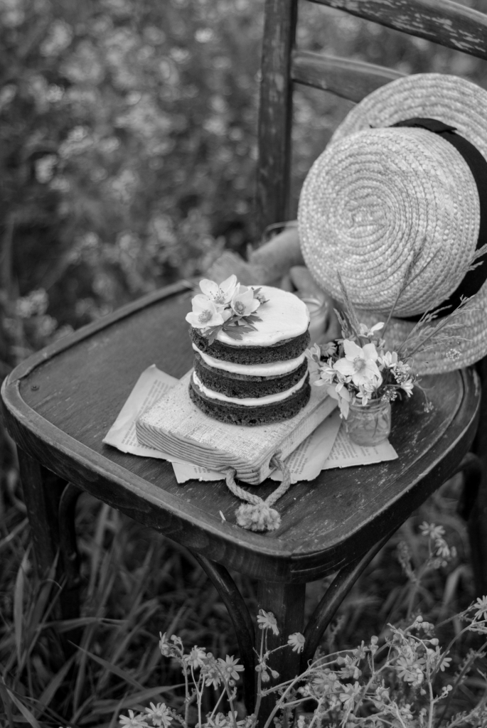 Straw hat, cake, small bouquet of flowers on chair