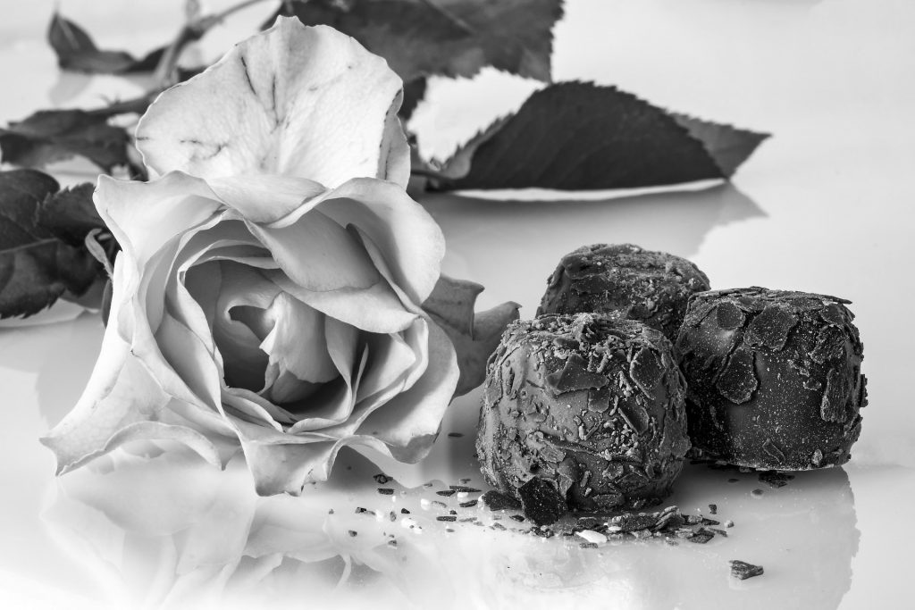 Black and white image of rose and chocolate truffles